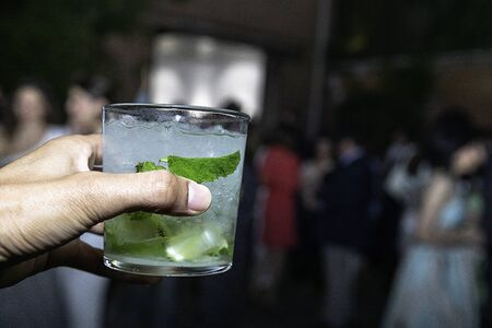 Hand celebrating a toast with a mojito with lemon, mint and ice at a event party
