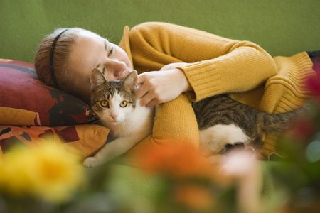 young woman and her cat on a green sofa