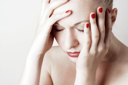 Woman With Headache. Red lips and nails. White background.