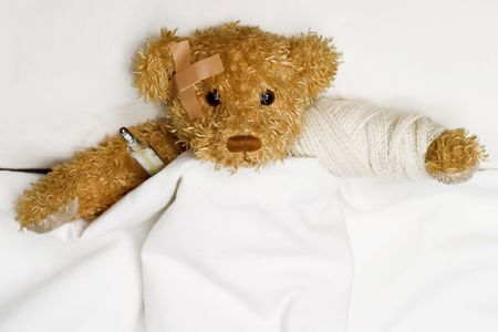 Teddy bear as a patient in hospitals bed with medical thermometer.