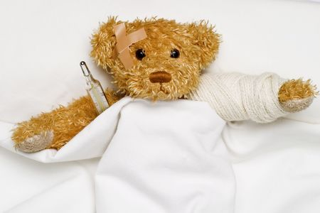teddy bear as a patient in bed with medical thermometer Stock Photo