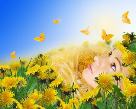 girl lying in grass on a meadow with dandelions Stock Photo