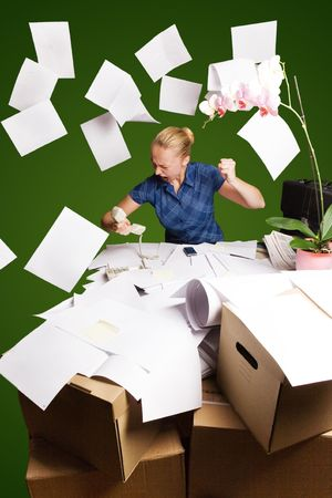 messy desk:   businesswoman in her office and flying paper sheets; green background Stock Photo
