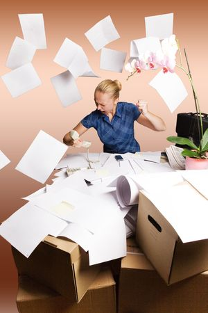 messy desk:   businesswoman in her office and flying paper sheets Stock Photo