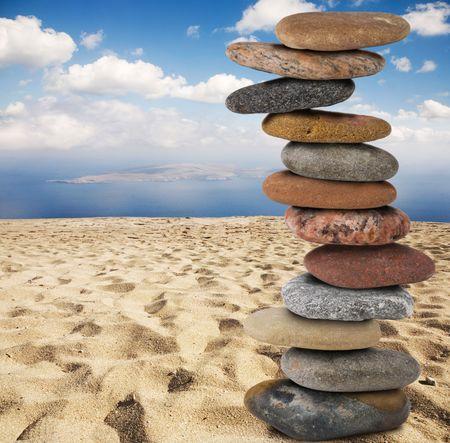 twelve zen stones stack on yellow sand