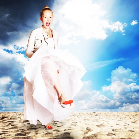 bride on the beach - wearing wedding dress, shoes with red hearts and white leather jacket photo