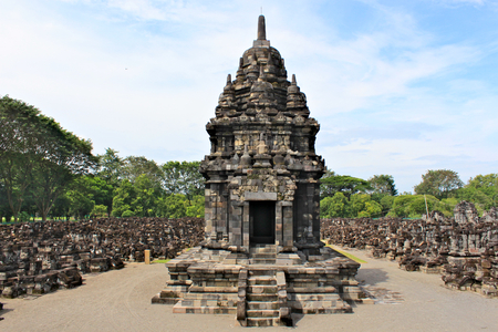 Sewu Temple is the second largest Buddhist temple complex in Java; built in 8th century; blue sky with white clouds and green trees around the ruins