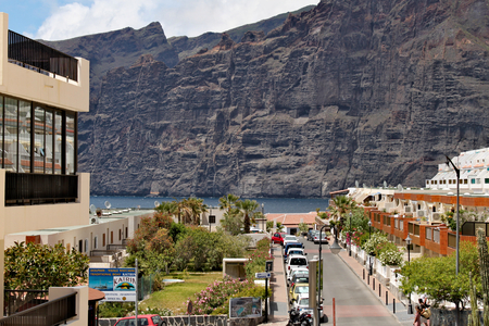Los Gigantes - coastlie with a range of volcanic mountaines; view from centre of town with one of main street Standard-Bild - 123681514