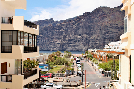Los Gigantes - coastlie with a range of volcanic mountaines; view from centre of town with one of main street Standard-Bild - 123681517