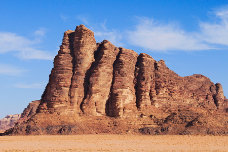 Seven pillars of wisdom on Wadi Rum desert in Jordan. Around red sand and clear blue sky with few clouds. Standard-Bild - 127499355