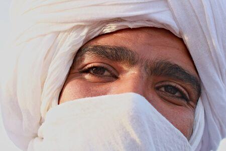 Head of Tuareg in white turban with black eyes Standard-Bild - 128140468
