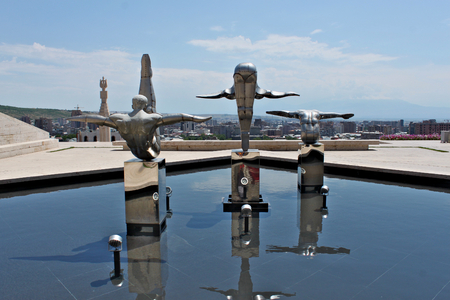 Armenia, Yerevan; July 9th 2014 - Modern art. Stainless steel sculptures of three athletes on top of Cascades in front of entrance door to a museum in Yerevan. Panarama of the city. Standard-Bild - 123681519