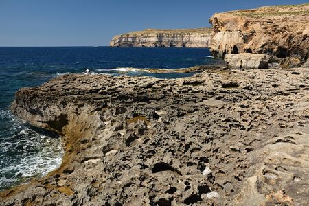 Dwejra Bay, with its dramatic coastal formations and sea spilling over the rocks, is a magical attraction. Here you can swim in the spectacular deep sea of the bay Standard-Bild - 127499364