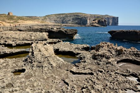 Dwejra Bay, with its dramatic coastal formations and sea spilling over the rocks, is a magical attraction. Here you can swim in the spectacular deep sea of the bay Standard-Bild - 127499368