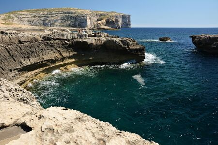 Dwejra Bay, with its dramatic coastal formations and sea spilling over the rocks, is a magical attraction. Here you can swim in the spectacular deep sea of the bay Standard-Bild - 127499365