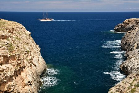 Wied il-Ghasri gorge with clean water surrounded by high clifs; sail boat on the sea Standard-Bild - 127499373