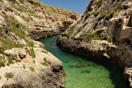 Wied il-Ghasri gorge with clean green water surrounded by high clifs; 250m long Standard-Bild - 127499374