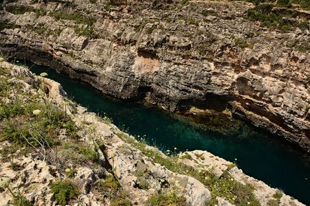 Wied il-Ghasri gorge with clean green water surrounded by high clifs; 250m long Standard-Bild - 127499809