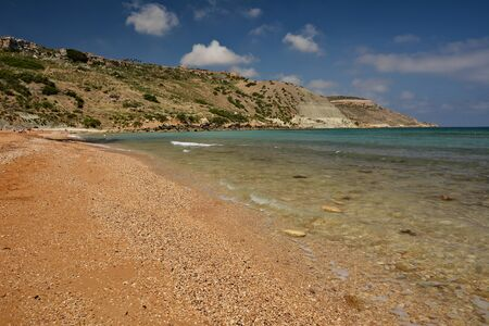 Ramla Bay - sandy beach with red send, turquoise water os sea and mountains at the background Standard-Bild - 127499801