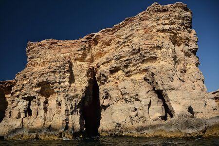 High cilfs with caves on Cominotto Island, near famous Comino Island Standard-Bild - 127499804