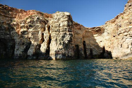 High cilfs with caves on Cominotto Island, near famous Comino Island Standard-Bild - 127499803