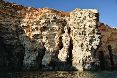 High cilfs with caves on Cominotto Island, near famous Comino Island 免版税图像