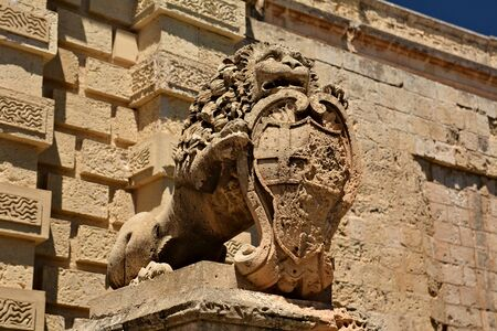 Sculpture of a lion in front of the old bridge with main gate to the Old Town of Mdina; tourists walking on the bridge