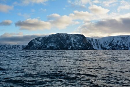Nordkapp is a municipality in Norway. It is 307-metre-high cliff that is commonly referred to as the northernmost point of Europe. However, the true northernmost point of the European mainland is Cape Nordkinn. View on snowy hills from a sailing boat 版權商用圖片