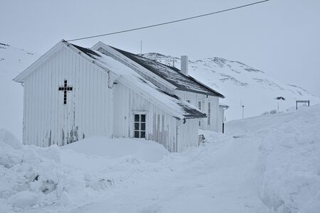 White, wooden church -  parish church of the Church of Norway in Nordkapp Municipality duirn winter time. At the background hills full of snow. Stock Photo