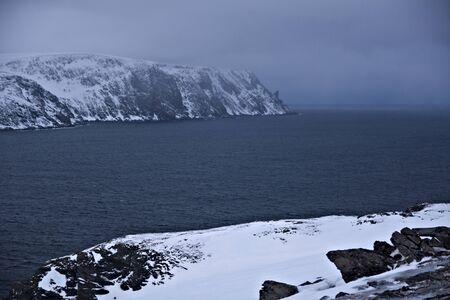 View on Nordkapp from Kirkeporten - rocky snowy hills above Skarsvag village