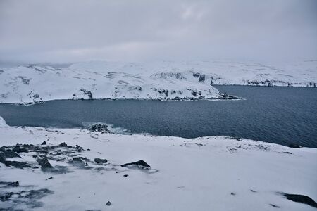 View from Kirkeporten - rocky snowy hills above Skarsvag village in the Nordkapp municipality.