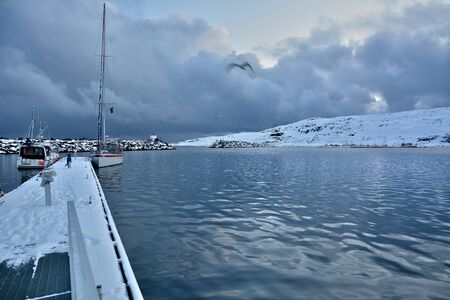 Sailing boat in a bay in Norway during winter time. Snowy hills at the background.