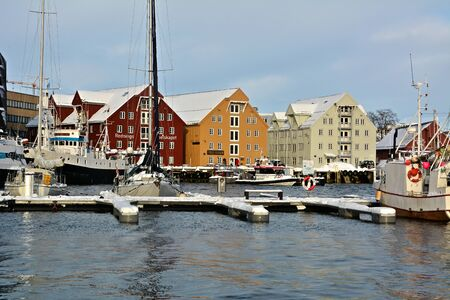 Port of Tromso with sail boats on water. At the background traditional colorful buildings of the town. Banco de Imagens