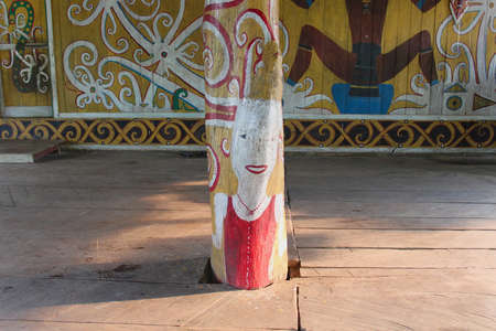 Decorative wooden column in long house in Merasa village on Bornego. Symbols of Dayak tribe people. Wooden decorated paterns.