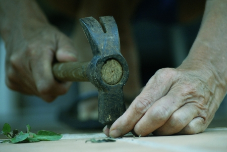 Older person working with hammer Stock Photo
