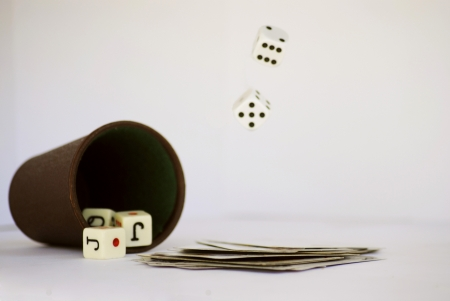 Cube dice on the table with a stack of cards and dice falling Stock Photo