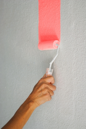 Painting pale pink colour wall with paint roller