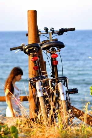 A couple of bikes parked by the sea with a girl from behind photo