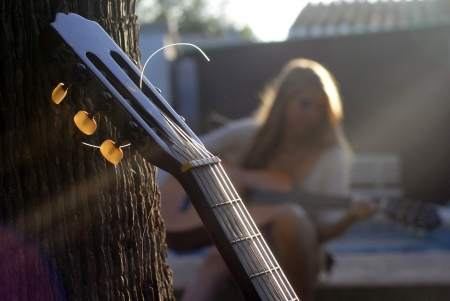 Guitar holding in a tree while a cute girl from behind is playing the guitar Stock Photo
