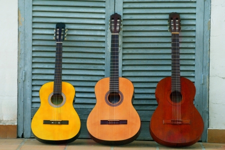 Three sets of classical guitars with different colors resting on a blue door