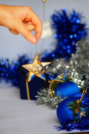 hand catching a christmas star with ornaments behind