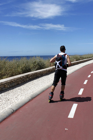 bikeway: guy skating in-line near the sea, in Portugal