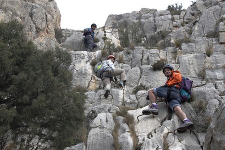 스페인에서 via ferrata를하고있는 세 명의 산악인들