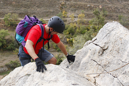 concentrate on: guy concentrate doing a via ferrata in Spain Stock Photo