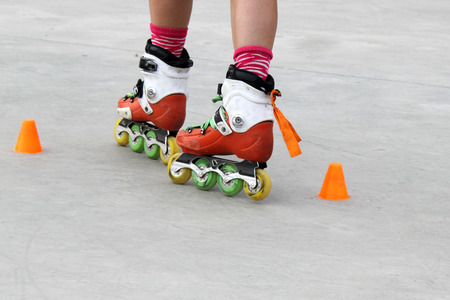 turning: girl turning while skating with cones Stock Photo