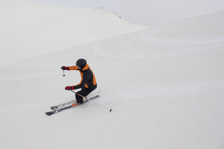 skidding: skier hoping tails while skiing in a ski slope Stock Photo