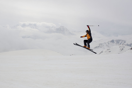 skier jumping: skier jumping with a range mountain background Stock Photo