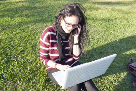 socialise: woman with her laptop and smartphone on the grass