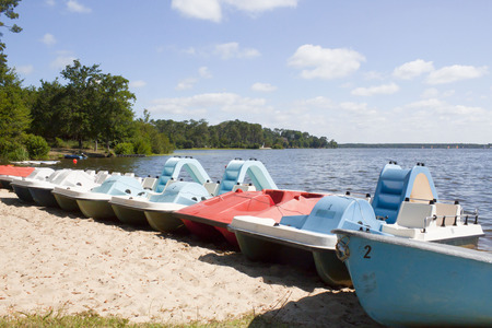 pedalos boats in the sand in front of a lake in a sunny day Stock Photo