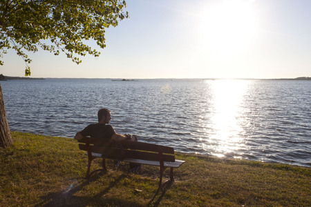 sitted: skater watching a sunset sitted in a bench near a lake